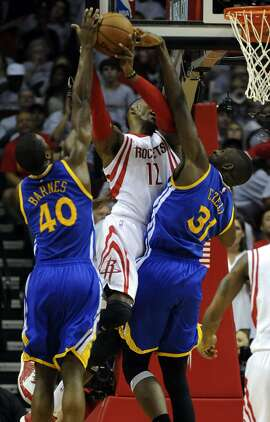 Houston Rockets center Dwight Howard #12 drives to the basket as Golden State Warriors forward Harrison Barnes #40 and Golden State Warriors center Festus Ezeli #31during the second quarter of Game 3 of the Western Conference Finals, Saturday, May 23, 2015, at Toyota Center in Houston, TX.