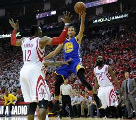 Golden State Warriors guard Stephen Curry #30 shoots past Houston Rockets center Dwight Howard #12 during the second quarter of Game 3 of the Western Conference Finals, Saturday, May 23, 2015, at Toyota Center in Houston, TX.