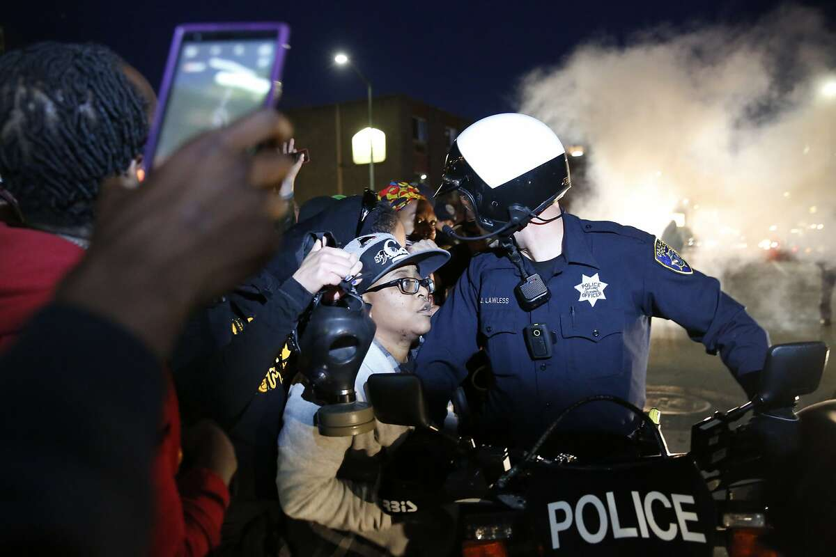 A flash bang grenade goes off as protesters push against Oakland police as they attempt to continue marching past 3rd and Washington during a rally and march called for by the Black Youth Project to protest the