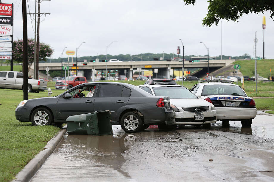 Cars, including a San Marcos Police unit, remain in the middle of Bugg Road after flooding affected the area in San Marcos, Sunday, May 24, 2015. Heavy rains fell throughout Saturday overflowing the Blanco River and flooding residents in the San Marcos Mobile Home Park. Photo: JERRY LARA, San Antonio Express-News / © 2015 San Antonio Express-News