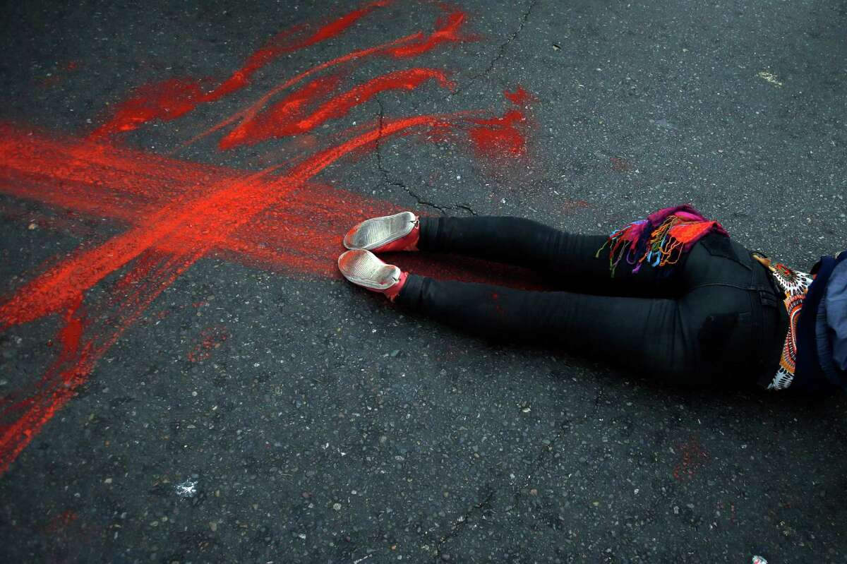 A protester performs the symbolic death of a student demonstrator during a march near Congress where Chile's President Michelle Bachelet gives her annual address in Valparaiso, Chile, Thursday, May 21, 2015. Demonstrators are protesting the death of two students killed during an education reform march last week in Valparaiso and demanding more involvement in education reform. (AP Photo/Luis Hidalgo)