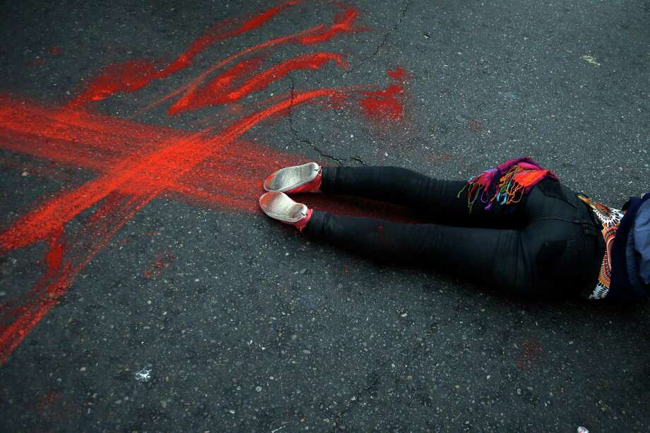 A protester performs the symbolic death of a student demonstrator during a march near Congress where Chile's President Michelle Bachelet gives her annual address in Valparaiso, Chile, Thursday, May 21, 2015. Demonstrators are protesting the death of two students killed during an education reform march last week in Valparaiso and demanding more involvement in education reform. (AP Photo/Luis Hidalgo) Photo: Luis Hidalgo, Getty Images  / AP