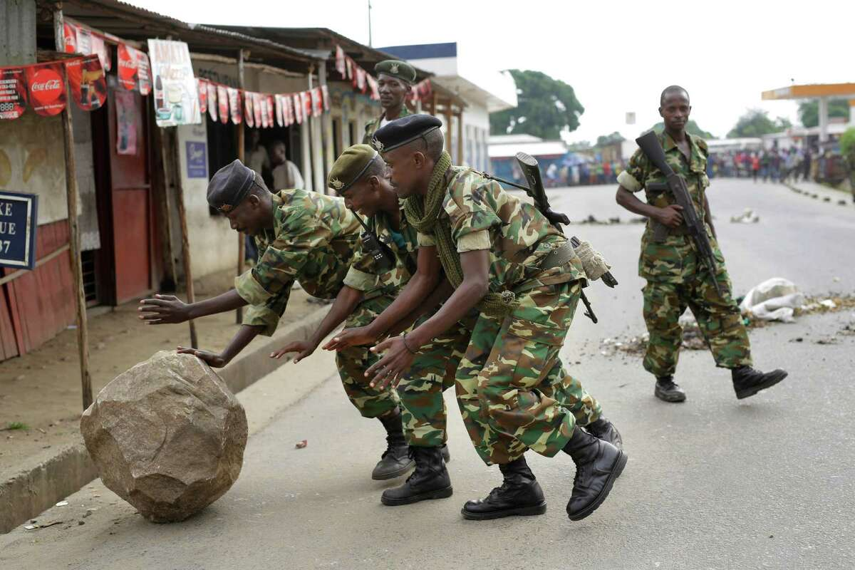 Soldiers clear a roadblock set by demonstrators in the Cibitoke neighborhood of Bujumbura, Burundi, Friday May 22, 2015. Two protesters in Burundi were shot dead Thursday, said the Red Cross, as pitched battles in the capital escalated between police and demonstrators opposed to President Pierre Nkurunziza's bid for a third term. (AP Photo/Jerome Delay)