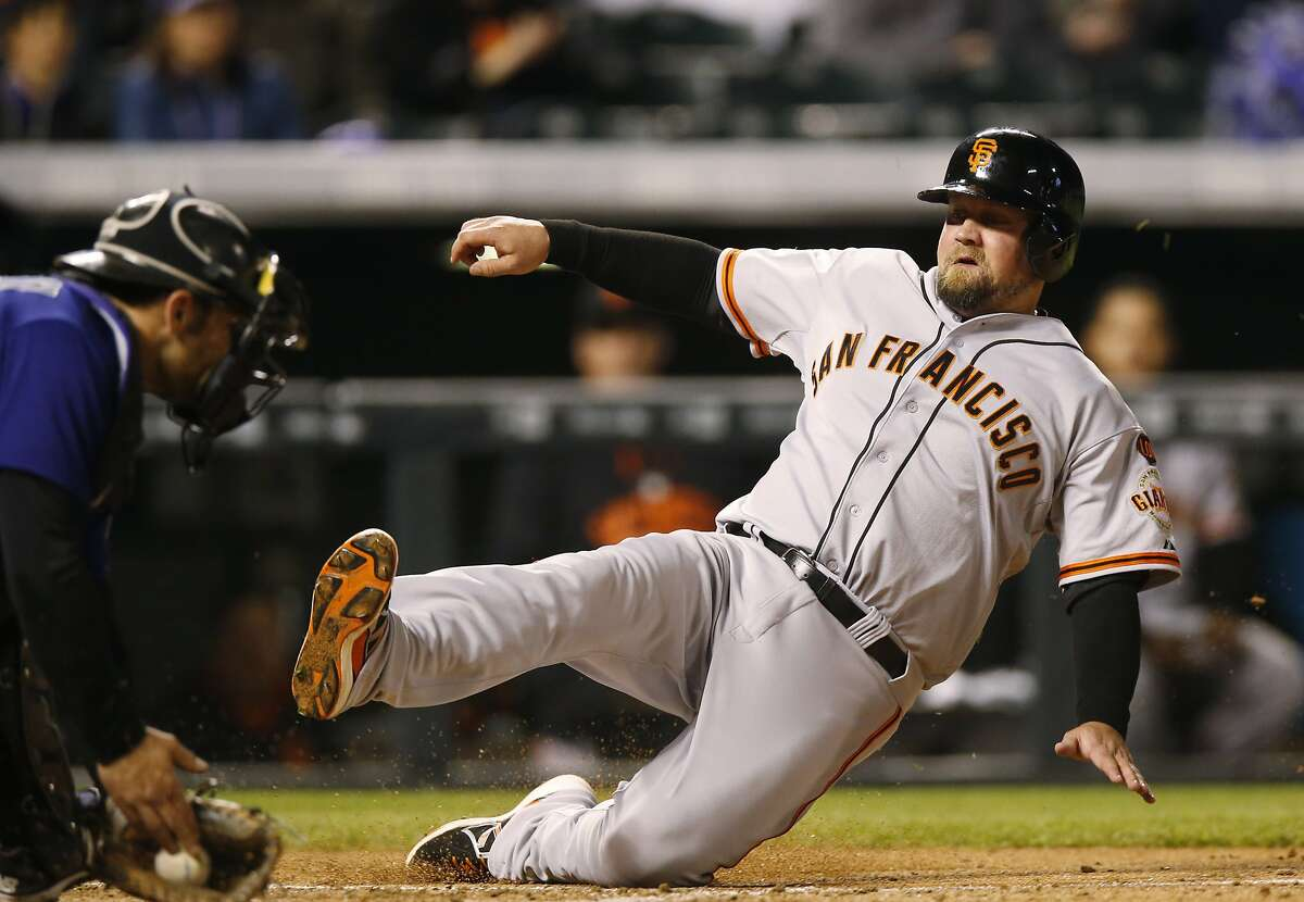 Colorado Rockies catcher Michael McKenry, left, applies the tag to put out San Francisco Giants' Casey McGehee at home plate during the fifth inning of the second game of a baseball doubleheader Saturday, May 23, 2015, in Denver. (AP Photo/David Zalubowski)