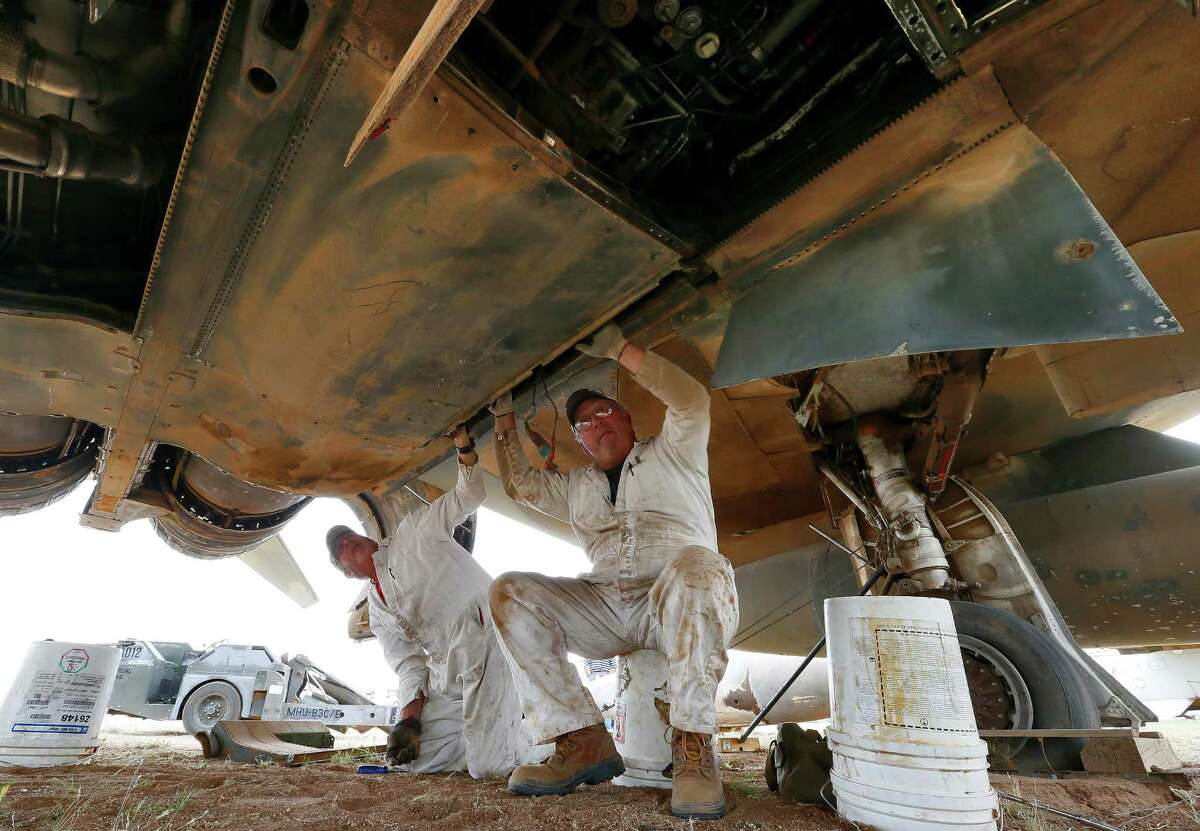 Demilitarization work leads Phil Kovaric, right, and Dennis Varney remove the missle rails from an F4 Phantom slated for destruction at the 309th Aerospace Maintenance and Regeneration Group boneyard, Thursday, May 21, 2015, in Tucson, Ariz. The 309th is the United States Air Force's aircraft and missile storage and maintenance facility and provides long and short-term aircraft storage, parts reclamation and disposal.
