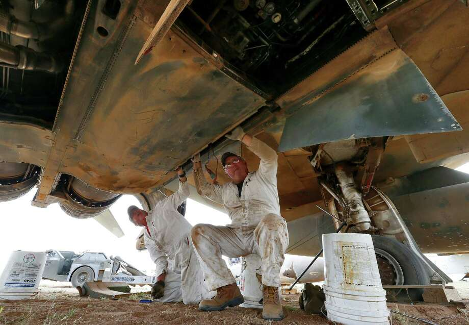 Demilitarization work leads Phil Kovaric, right, and Dennis Varney remove the missle rails from an F4 Phantom slated for destruction at the 309th Aerospace Maintenance and Regeneration Group boneyard, Thursday, May 21, 2015, in Tucson, Ariz. The 309th is the United States Air Force's aircraft and missile storage and maintenance facility and provides long and short-term aircraft storage, parts reclamation and disposal. Photo: Matt York, AP / AP