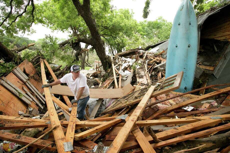 Keith McNabb looks at the damage to his friend Mike Cook's house on Stone Canyon Street on the banks of the Blanco River near Wimberley, Texas on Sunday May 24, 2015. Flooding in Texas and Oklahoma has led to numerous evacuations. (Jay Janner/Austin American-Statesman via AP) AUSTIN CHRONICLE OUT, COMMUNITY IMPACT OUT, INTERNET AND TV MUST CREDIT PHOTOGRAPHER AND STATESMAN.COM, MAGS OUT Photo: Jay Janner, AP / Austin American-Statesman