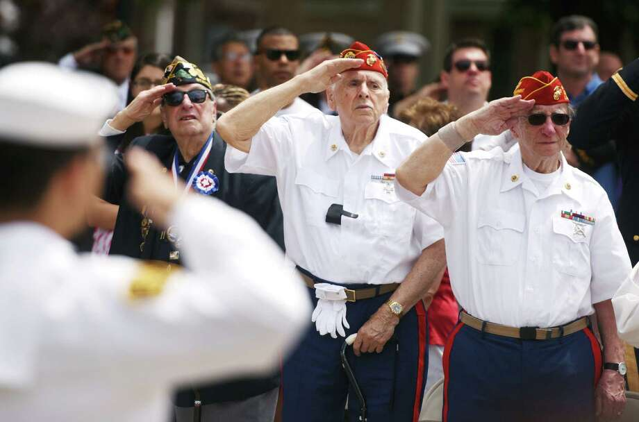 Veterans Carmine Vaccaro, left, Vito Ottaviano, center, and Kurt Zimbler salute the flag during the Memorial Day ceremony at Veterans Park in Stamford, Conn. Sunday, May 24, 2015.  The parade was led by the Stamford Fire Department Honor Guard and featured WWII Iwo Jima survivor John S. Geas as the Grand Marshal.  The parade concluded with a ceremony at Veteran's Park to remember those who lost their lives in combat. Photo: Tyler Sizemore / Greenwich Time