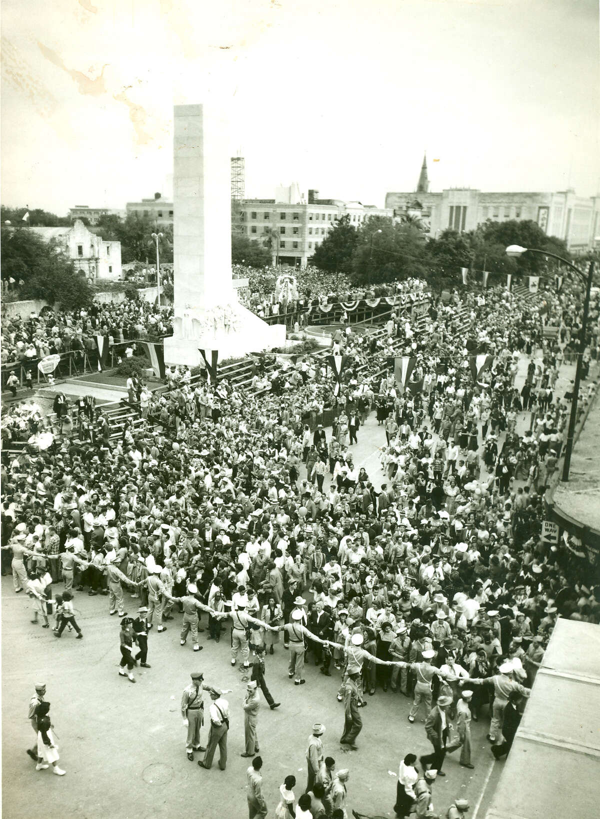 During Fiesta 1950, police engage in crowd control around the Alamo Cenotaph after a parade.