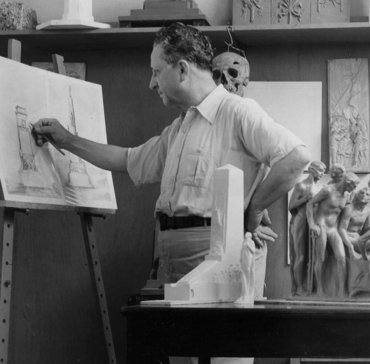 Sculptor Pompeo Coppini works on an illustration of the Alamo Cenotaph, which now stands in front of the Alamo in Alamo Plaza. To his side is a preliminary model of the sculpture.