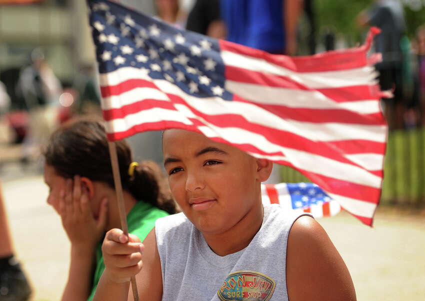 Aidan Grant, 9, watches the annual Memorial Day Parade with his cousin Bridget Negron, 10, both of Milford, on River Street in downtown Milford, Conn, on Sunday, May 24, 2015.
