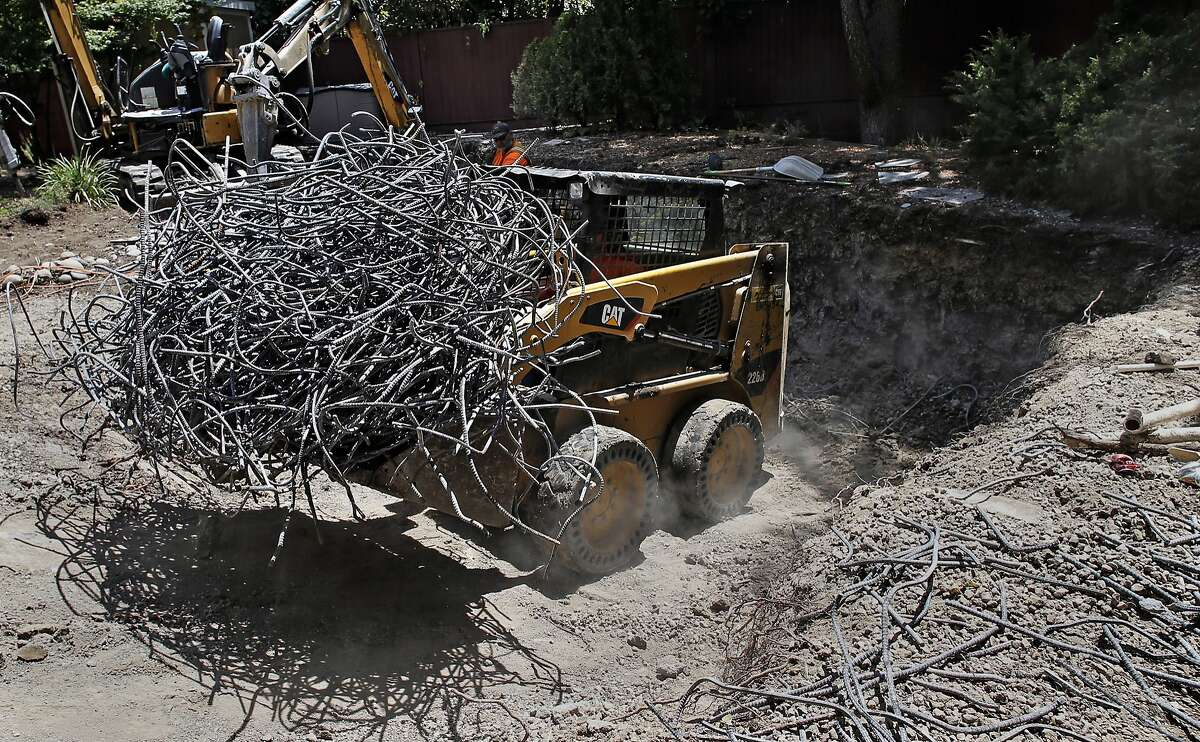 Miguel Gutierrez, with the construction company Dig & Demo removes rebar to be recycled as a backyard pool is removed for a homeowner in Pleasant Hill, Calif., largely to save water during the drought as seen on Thurs. May, 21, 2015.