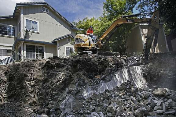 Miguel Gutierrez, with the construction company Dig & Demo operates a jack hammer to remove rebar and concrete as a backyard pool is removed for a homeowner in Pleasant Hill, Calif., largely to save water during the drought as seen on Thurs. May, 21, 2015.