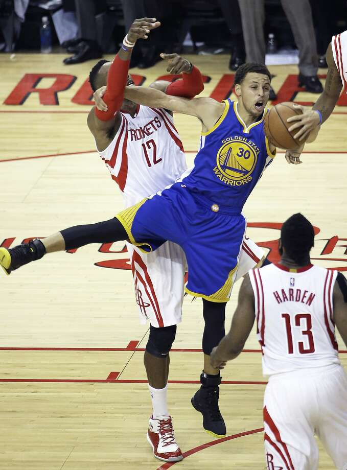 Stephen Curry controls a rebound with one hand and fends off Dwight Howard with the other. Photo: Pat Sullivan, Associated Press