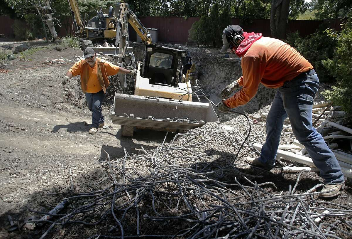 Russell Ellison, (left) and Miguel Gutierrez with the construction company Dig and Demo, gather rebar to be recycled as they remove an entire backyard pool for a homeowner in Pleasant Hill, Calif., largely to save water during the drought as seen on Thurs. May, 21, 2015.