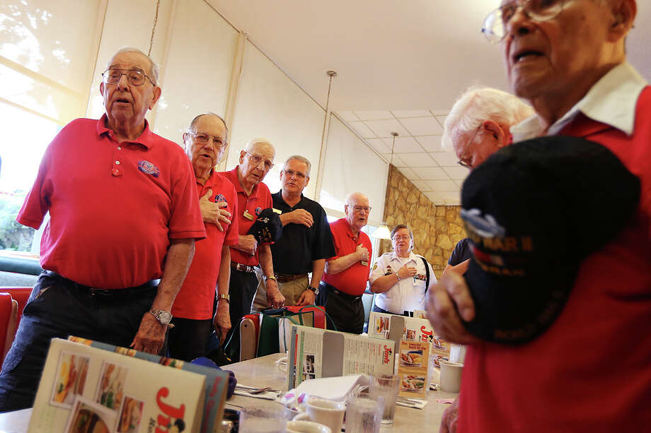 World War II veterans salute the flag as they gather for breakfast at JimÕs Restaurant in Balcones Heights, Wednesday, May 20, 2015. On the left is Vincent Losada, 90, who lost his arm as a bombardier in a B-17 while on his 25th bombing mission over Germany in May 1948. The breakfast is one of nine throughout the San Antonio area, including Kerrville, organized by local pharmacist Russell Minor. He said that around 100 veterans participate. Photo: JERRY LARA /San Antonio Express-News / © 2015 San Antonio Express-News