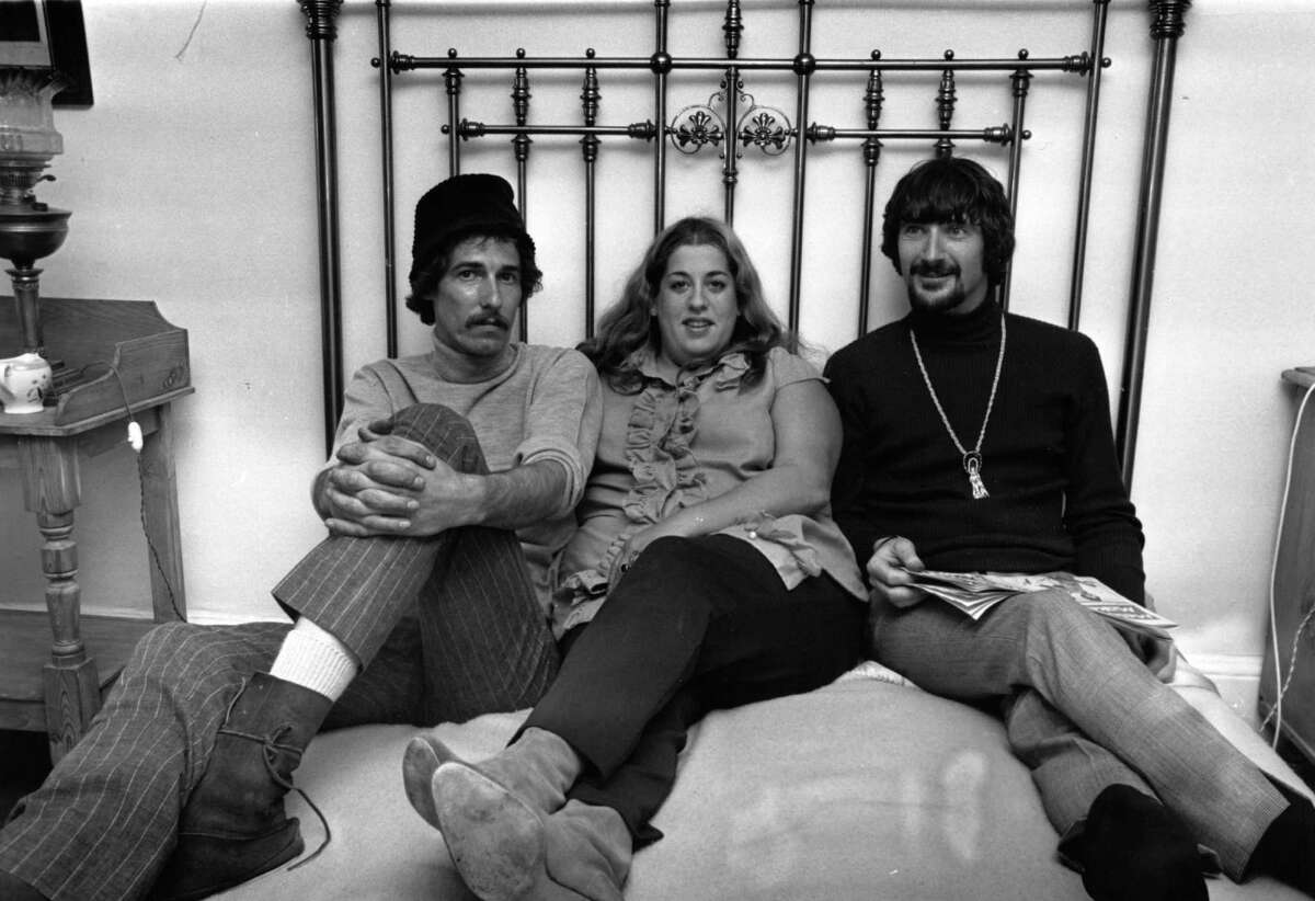 From left to right; American musicians John Phillips (1935 - 2001), Mama Cass Elliot (1941 - 1974), and Canadian-born Denny Doherty, of the California folk pop group The Mamas and the Papas reclining on a bed, June 15, 1966. (Photo by Express/Express/Getty Images)