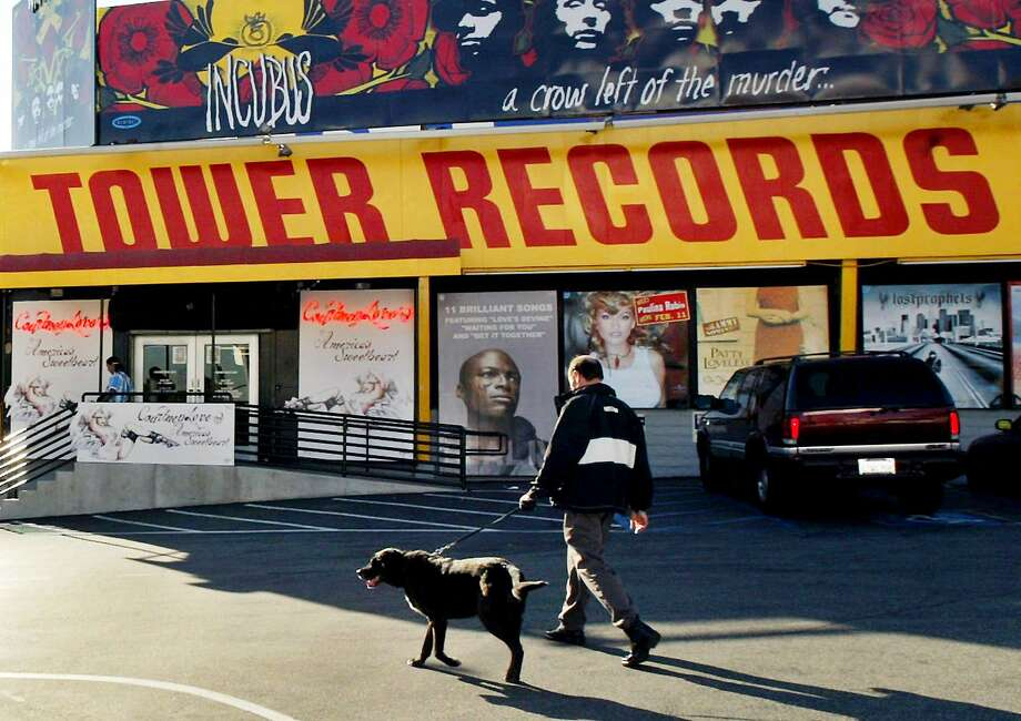 "FILE - In this Feb. 9, 2004 file photo, a pedestrian walks through the parking lot of Tower Records in Los Angeles. ""All Things Must Pass,"" a documentary by Colin Hanks about Tower Records, the retail store that dominated for decades before filing for bankruptcy in 2006, earned at standing ovation at the South by Southwest festival on Tuesday, March 17, 2015. (AP Photo/Ric Francis, File) Photo: Ric Francis, Associated Press"