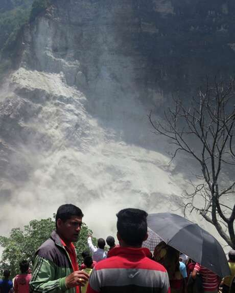 People gather near the site of a landslide north of Beni Bazaar in Nepal. A sudden collapse of the natural dam could cause a wall of water that would wash away everything in its path. Photo: M.B. Astha /Associated Press / AP