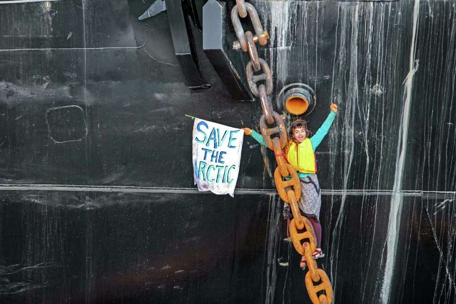 Chiara D'Angelo remains suspended from the anchor chain of the Royal Dutch Shell support ship Arctic Challenger in the harbor at Bellingham, Wash. She is protesting Shell's plan for Arctic drilling. Photo: Reese Semanko /Associated Press / Reese Semanko