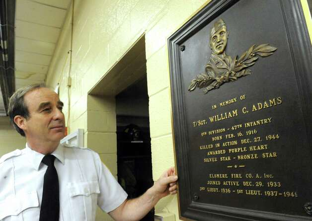 John Murphy, president of the Elsmere Fire Company, looks at the a plaque of the late William Adams, a WWII vet killed in action, hung at the fire hall on Friday May 22, 2015 in Delmar, N.Y. (Michael P. Farrell/Times Union) Photo: Michael P. Farrell / 00031949A