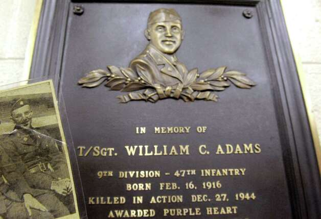 A plaque of the late William Adams, a WWII vet killed in action, hangs at the Elsmere Fire Company on Friday May 22, 2015 in Delmar, N.Y. (Michael P. Farrell/Times Union) Photo: Michael P. Farrell / 00031949A