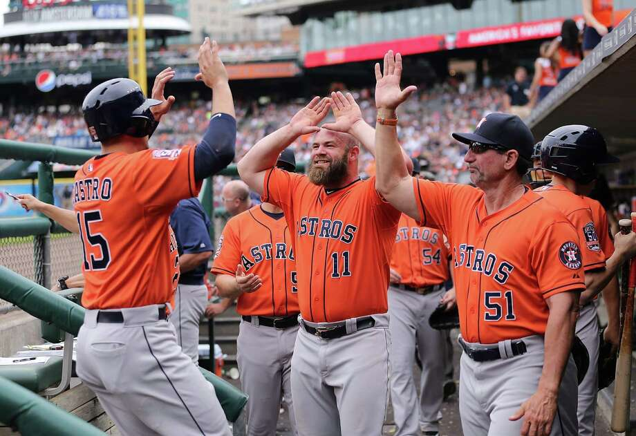 Jason Castro, left, celebrates his seventh-inning, bases-loaded single that drove in two runs and gave the Astros the lead for good in a 10-8 win over Detroit. Photo: Leon Halip, Stringer / 2015 Getty Images