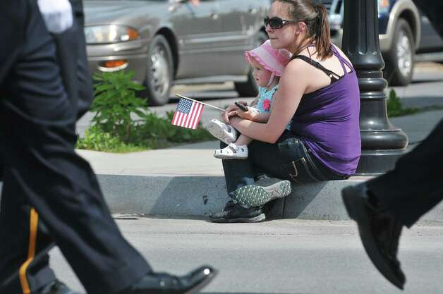 Vanessa Adalian of Castelton holds her daughter, Emma, 1, as they watch the Rensselaer Memorial Day Parade on Sunday, May 24, 2015, in Rensselaer, N.Y.   (Paul Buckowski / Times Union) Photo: PAUL BUCKOWSKI / 00031978A