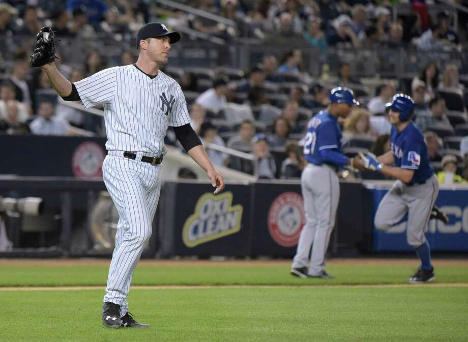 New York Yankees pitcher Chris Capuano, left, reacts as Texas Rangers' Adam Rosales, right, celebrates with third base coach Tony Beasley as he rounds the bases with a two-run home run during the second inning of a baseball game Sunday, May 24, 2015, at Yankee Stadium in New York. (AP Photo/Bill Kostroun) ORG XMIT: NYY113 Photo: Bill Kostroun / FR51951 AP