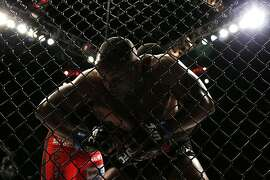 Daniel Cormier, foreground, and Anthony Johnson wrestle against the fence during their light heavyweight title bout at UFC 187 Saturday, May 23, 2015, in Las Vegas. (AP Photo/John Locher)