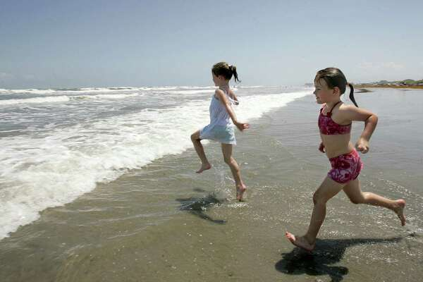 6-year-old Baylie Sides, left, and her cousin 6-year-old Alyssa McDaniel run into the water at a beach in Port Aransas.