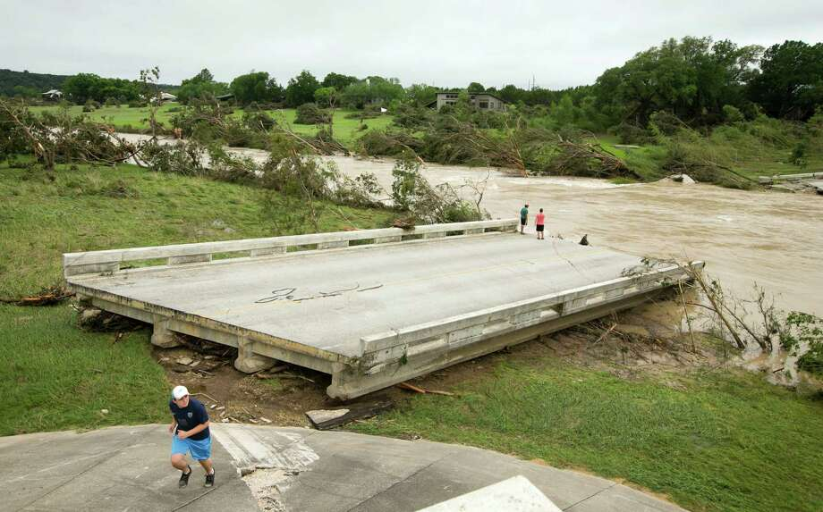 Left to right, Dustin McClintock, 19, of Wimberley,, Brandon Bankston, 18, of Blanco, Hesston Krause, 22, of Smithson Valley, look at the Fischer Store Road bridge over the Blanco River near Wimberley, Texas, which was destroyed in a flood on Sunday May 24, 2015. (Jay Janner/Austin American-Statesman via AP) AUSTIN CHRONICLE OUT, COMMUNITY IMPACT OUT, INTERNET AND TV MUST CREDIT PHOTOGRAPHER AND STATESMAN.COM, MAGS OUT Photo: Jay Janner, AP / Austin American-Statesman