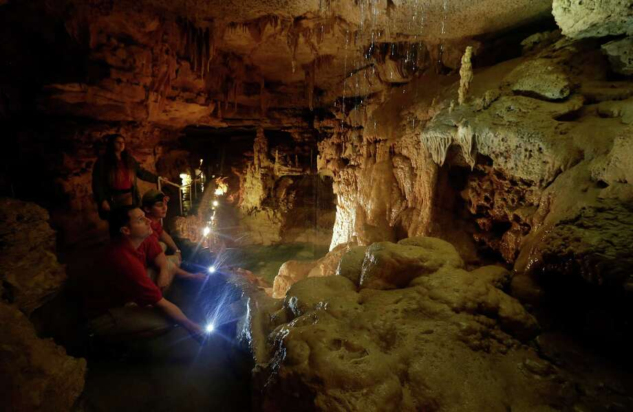 Travis Wuest (left), Vice President of Natural Bridge Caverns, and operations supervisor Dylan Ellis use flashlights to survey water filtering in a room called Emerald Lake on Saturday, May 23, 2015. Recent heavy rains have penetrated through the limestone formations that feed into the Trinity Aquifer - one of the largest groundwater resources in Texas. Wuest said he has seen a noticeable rise in water displacement in various areas inside the caverns. (Kin Man Hui/San Antonio Express-News) Photo: Kin Man Hui, Staff / San Antonio Express-News / ©2015 San Antonio Express-News