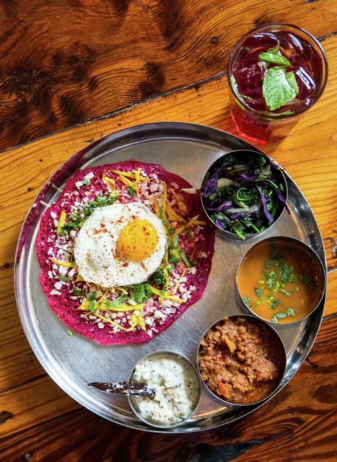 Pondicheri's beet uttapum, flat thick dosa with ginger and fresh coconut fried egg accompanied with keema, sautéed greens, sambhar and coconut chutney Photo: Nick De La Torre / © de la Torre Photos LLC