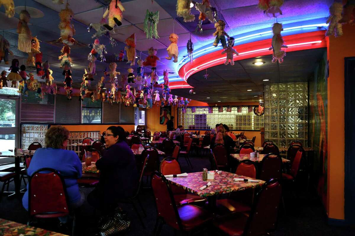 Interior of Lupita's Mexican Restaurant which is very colorful including a parrot jungle mural, and the entire ceiling festooned with pinatas, glass blocks and swooping neon adding light and color.