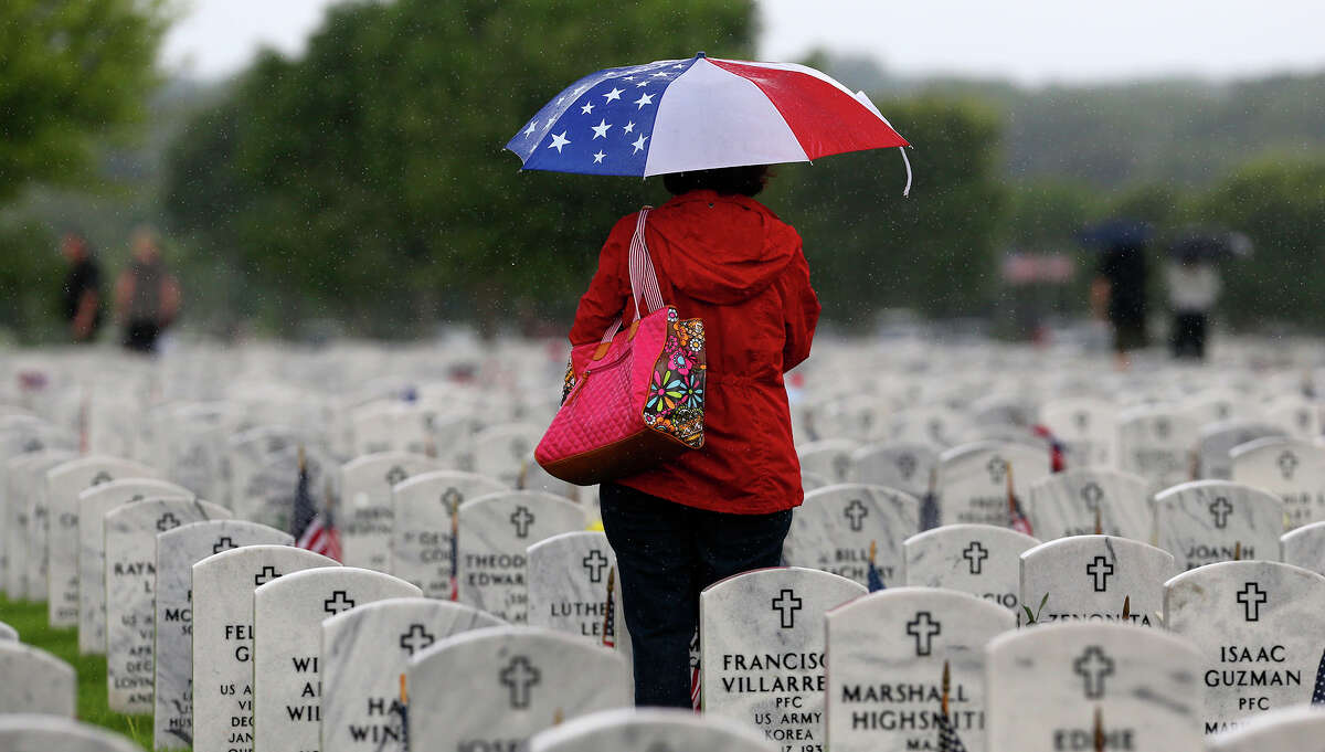 Janie Ramos tvisits her father's grave after the Memorial Day ceremony Monday May 25, 2015 at Fort Sam Houston National Cemetery. Her father, Joe J. Ramos, served in the Army during World War II.