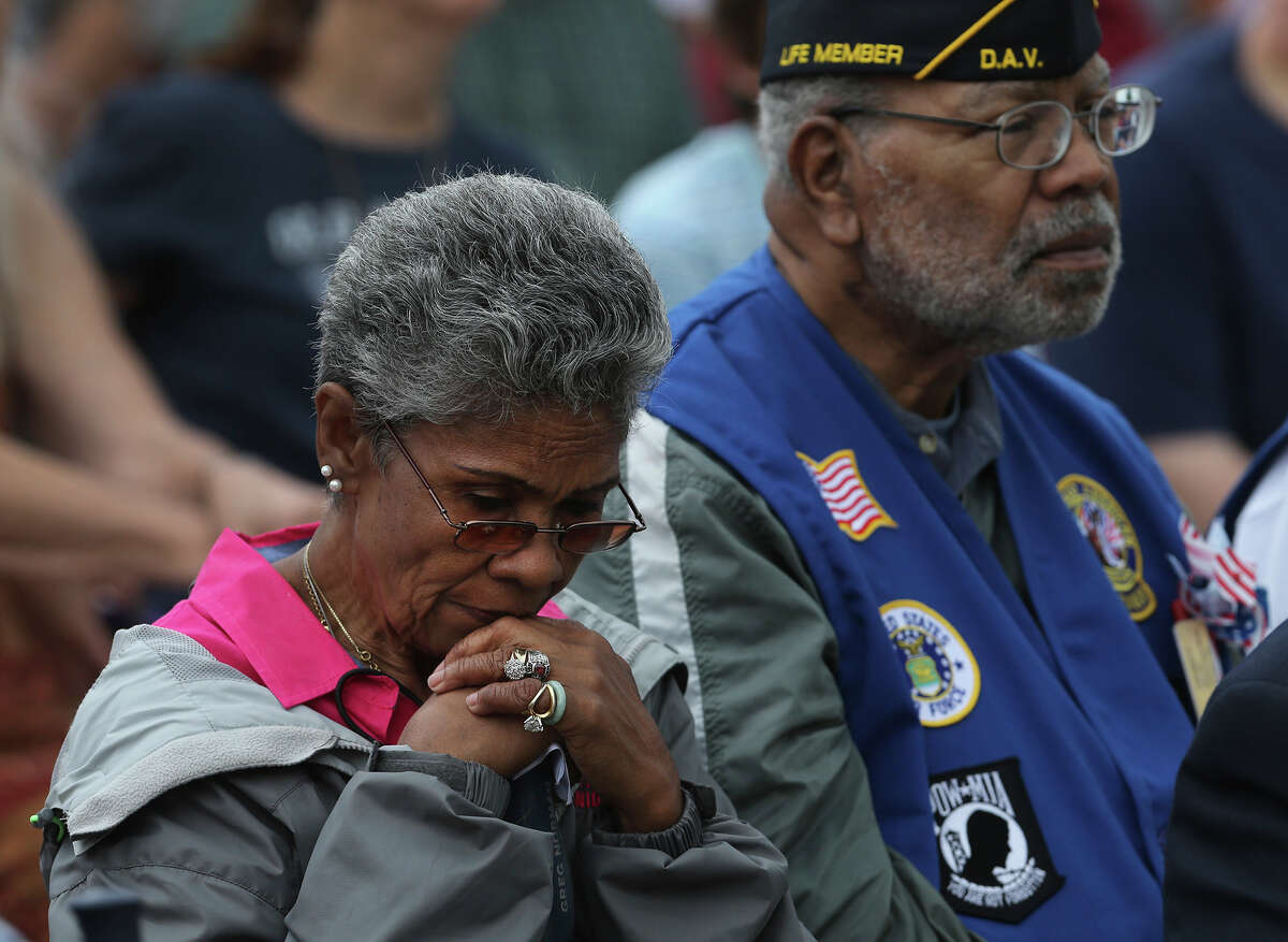 Malinda (cq) Ferguson (left) reflects during the Memorial Day ceremony held Monday May 25, 2015 at Ft. Sam Houston National Cemetery. Seated on the right is Louis Cousins, Sr. who served in the U.S. Air Force for 21 years.