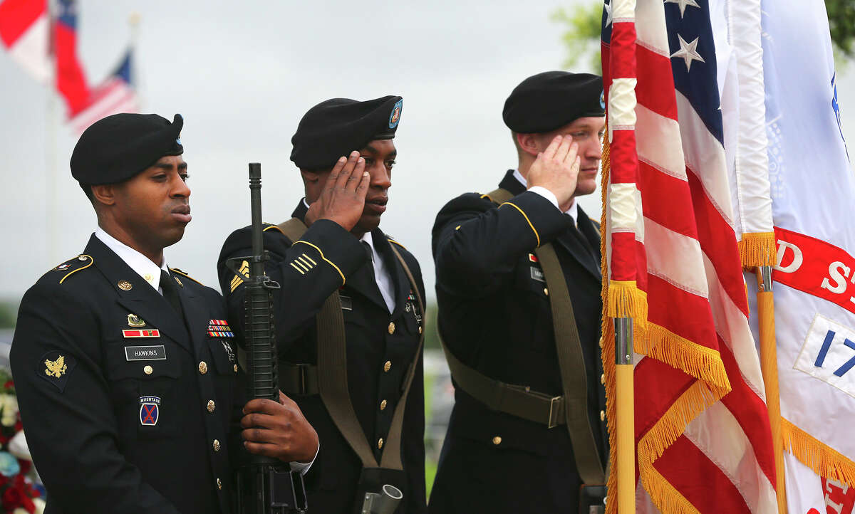 The color guard salutes and stands at attention Monday May 25, 2015 during the Memorial Day ceremony held at Ft. Sam Houston National Cemetery.