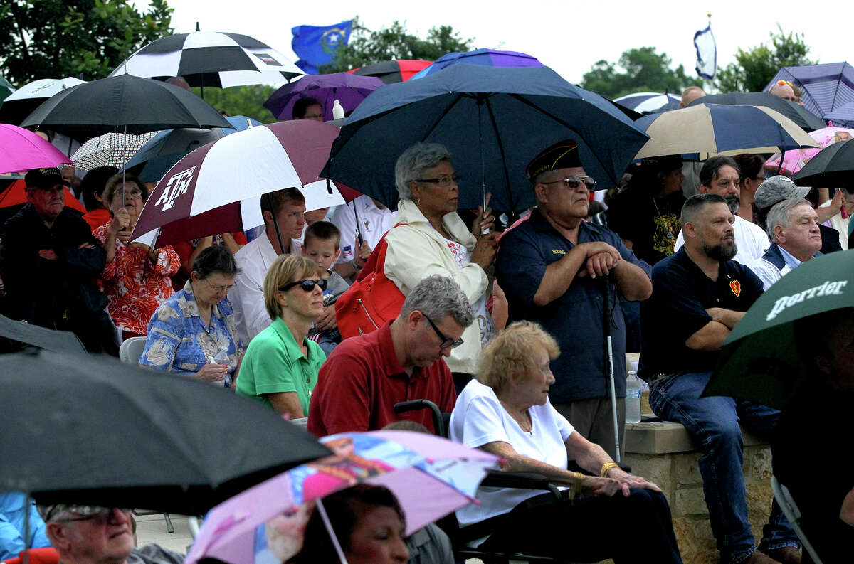 People watching the Memorial Day ceremony at Ft. Sam Houston National Cemetery Monday May 25, 2015 get their unbrellas out as showers move through the area.