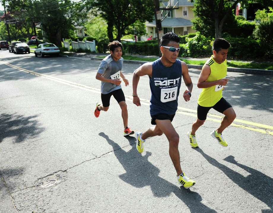 Race leaders Angel Confesor, left, of Brooklyn, N.Y., Jesus Zamora, center, of New York City, and Alejandro Ariza, of Brooklyn, N.Y., speed up a hill during the Jim Fixx Memorial Day 5-mile road race in Greenwich, Conn. Monday, May 25, 2015.  Ariza would go on to win the race with a time of 27:27, with Zamora and Confesor placing second and third.  The 51st annual race, sponsored by the Department of Parks and Recreation and Threads and Treads, traversed the town going down Greenwich Avenue and through Bruce Park before finishing at the Havemeyer Field track. Photo: Tyler Sizemore / Greenwich Time