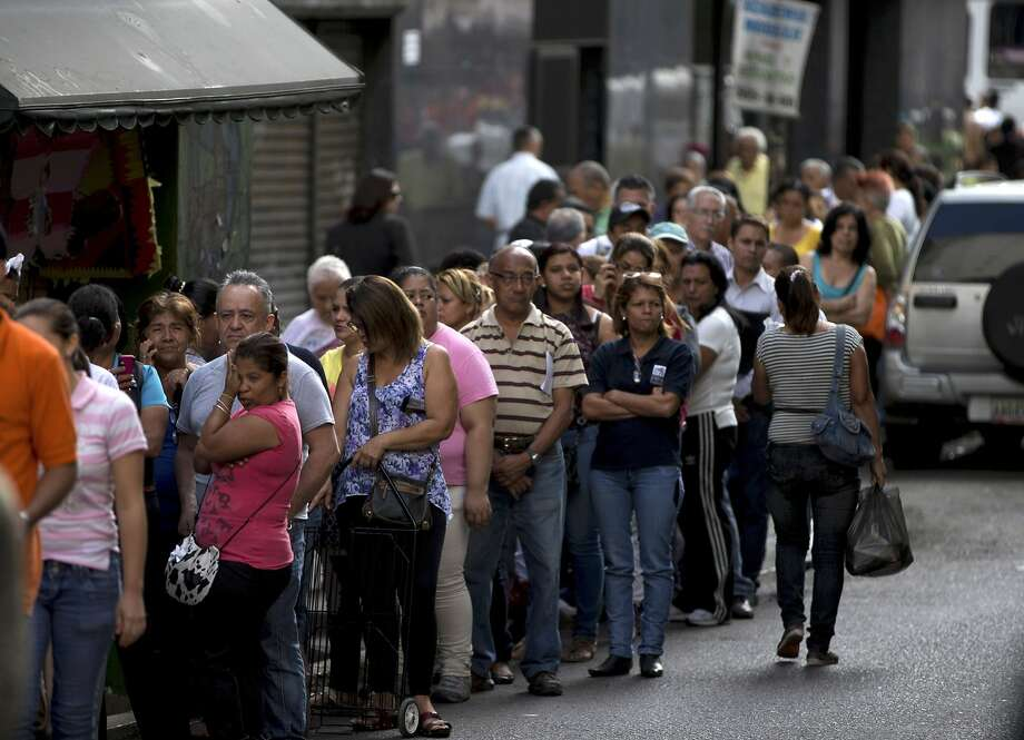 Shoppers line up outside a supermarket in downtown Caracas, Venezuela. Bas ic goods such as detergent and sugar are in demand during the economic crisis. Photo: Fernando Llano, Associated Press