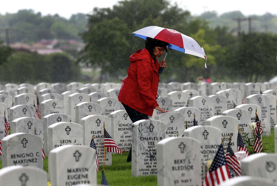 Janie Ramos touches her father's headstone after the Memorial Day ceremony Monday May 25, 2015 at Fort Sam Houston National Cemetery. Her father, Joe J. Ramos, served in the Army during World War II. Photo: John Davenport, Staff / San Antonio Express-News / ©San Antonio Express-News/John Davenport
