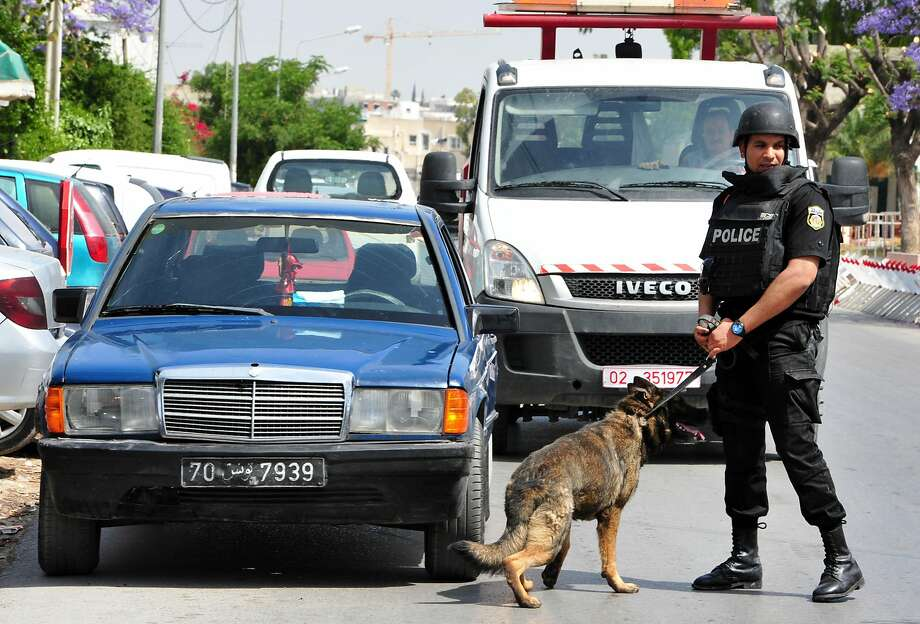 A police officer and his dog patrol near the scene of a shooting at the Bouchoucha barrack in Tunis, Tunisia, after a soldier opened fire on his peers. Seven soldiers were killed and 10 wounded before the shooter was slain, according to a Defense Ministry spokesman. Photo: Ali Dali, Associated Press
