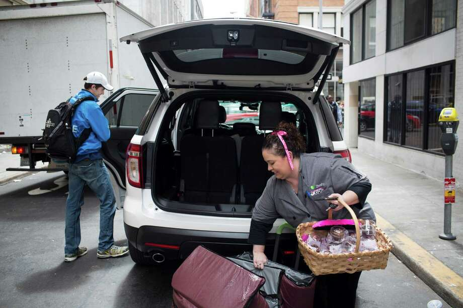 Rachel Powell of Vallejo loads catering supplies into the back of her car in San Francisco. Powell, who has two kids in school, uses her car to do work for both Zesty.com and Lyft. Photo: Tim Hussin /Special To The San Francisco Chronicle / ONLINE_YES