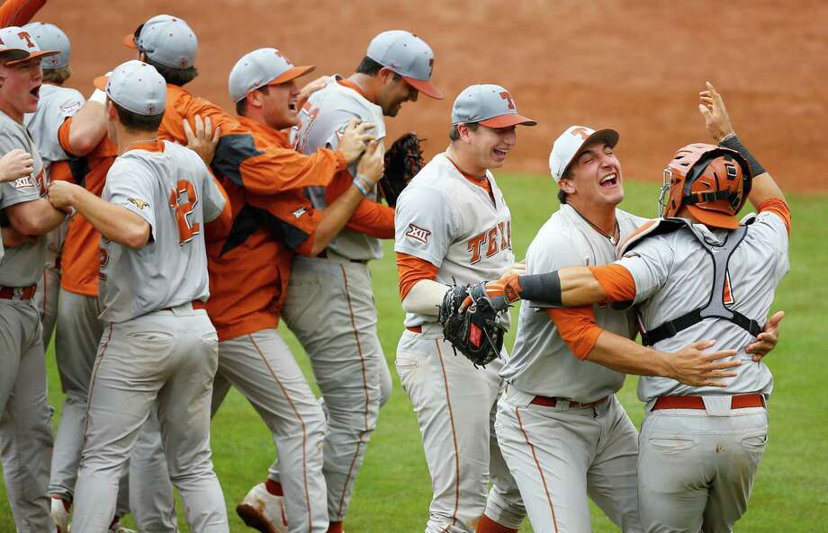 Texas' Michael Cantu, second from right, hugs catcher Tres Barrera, right, as Texas players celebrate after Texas defeated Oklahoma State in the championship game of the NCAA college Big 12 conference baseball tournament in Tulsa, Okla., on May 24, 2015. Texas won 6-3. Photo: Sue Ogrocki /Associated Press / AP