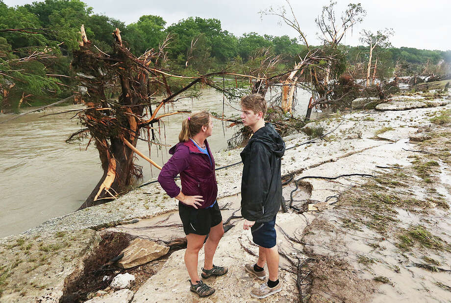 Shelly Guzal and her son, Grant, 17, stand by the Blanco River by where an A-frame house owned by the Carey family once stood in Wimberley, Texas, Monday, May 25, 2015. Corpus Christi resident Jonathan McComb, 36, and his family were guest in the house when it was swept away by floodwaters Saturday night. McComb was able to escape but his wife, Laura, 33, and their children, Leighton, 4 and Andrew, 6, are missing. Photo: JERRY LARA, Staff / San Antonio Express-News / © 2015 San Antonio Express-News