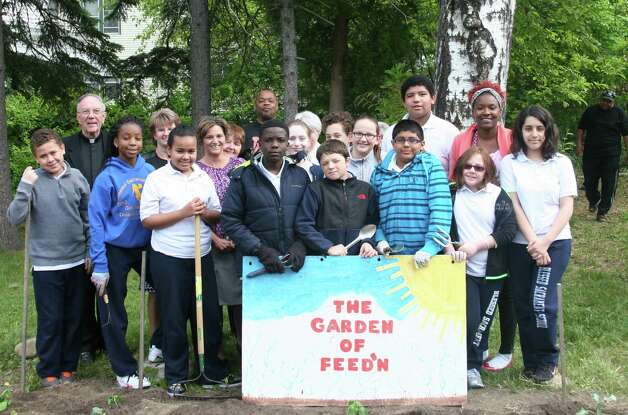 "Sixth-graders from Blessed Sacrament School visit the ""Garden of Feedin'"" in West Hill on May 15, 2015, to help rake and plant the garden. (Paul McAvoy)"