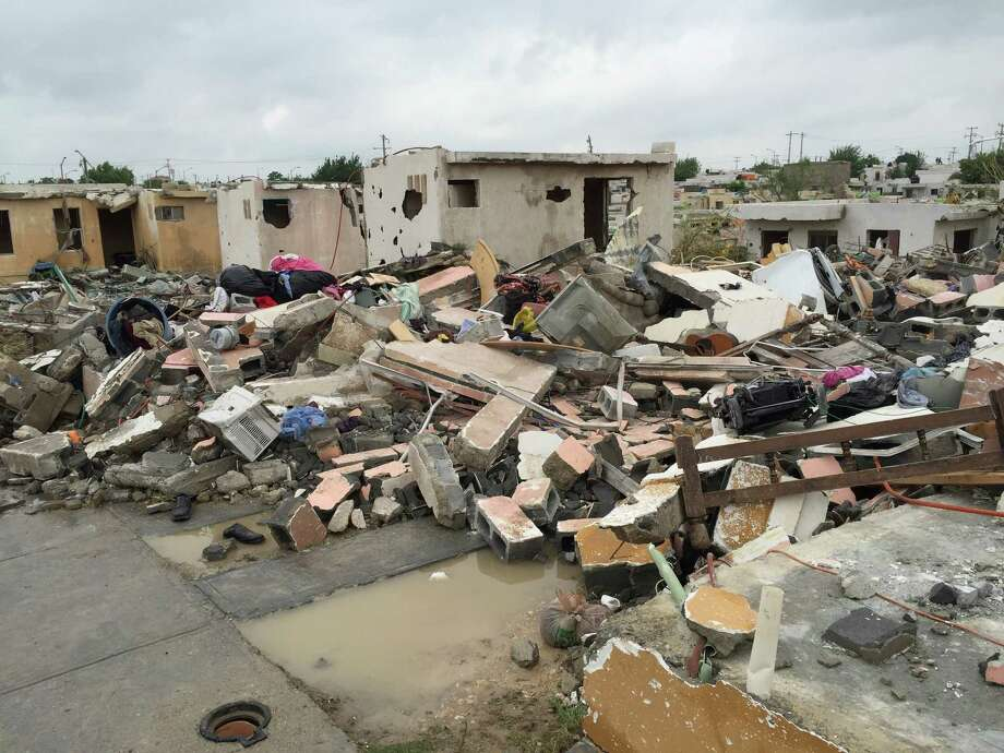 "Damaged homes stand next to others that were razed when a powerful tornado touched down in Ciudad Acuna, northern Mexico, Monday, May 25, 2015. The tornado raged through the city on the U.S.-Mexico border Monday, destroying homes and flinging cars like matchsticks. At least 13 people were killed, authorities said. The twister hit a seven-block area, which Victor Zamora, interior secretary of the northern state of Coahuila, described as ""devastated."" (AP Photo) Photo: Associated Press / AP"