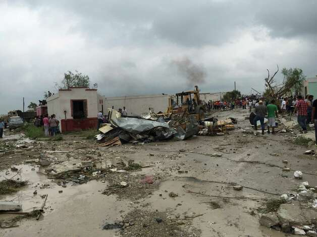 "A bulldozer clears away debris after a powerful tornado swept past in Ciudad Acuna, northern Mexico, Monday, May 25, 2015. A tornado raged through the city on the U.S.-Mexico border Monday, destroying homes and flinging cars like matchsticks. At least 13 people were killed, authorities said. The twister hit a seven-block area, which Victor Zamora, interior secretary of the northern state of Coahuila, described as ""devastated."" (AP Photo) ORG XMIT: XMEX102 / AP"