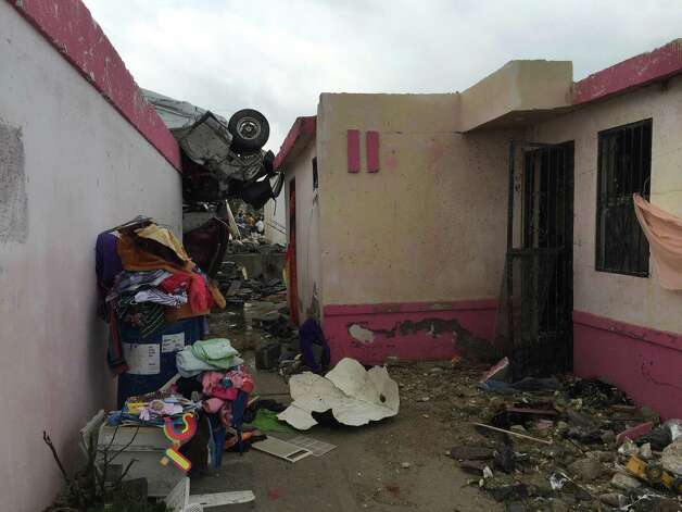 "A vehicle lies on the rooftop of a home after a powerful tornado swept past in Ciudad Acuna, northern Mexico, Monday, May 25, 2015. A tornado raged through a city on the U.S.-Mexico border Monday, destroying homes and flinging cars like matchsticks. At least 13 people were killed, authorities said. The twister hit a seven-block area, which Victor Zamora, interior secretary of the northern state of Coahuila, described as ""devastated."" (AP Photo) ORG XMIT: XMEX103 / AP"